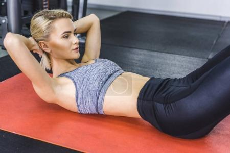 beautiful young woman doing abs crunches on yoga mat at gym
