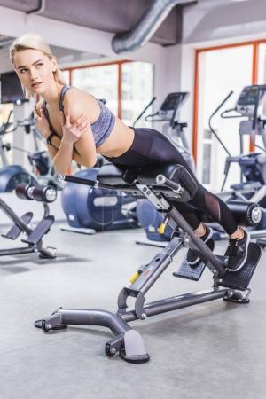 Photo pour Jeune femme sportive faisant l'exercice d'hyperextension sur la machine de gymnase - image libre de droit