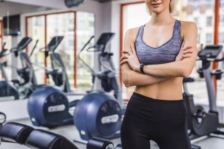 cropped shot of woman standing with crossed arms at gym in front of elliptical machines