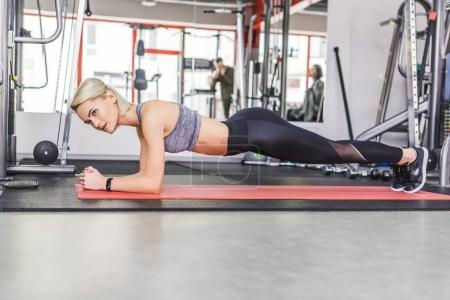 young athletic woman doing plank exercise on yoga mat at gym