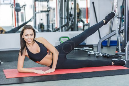 young woman doing exercise on yoga mat at gym