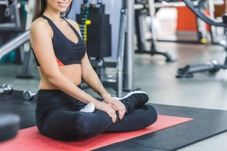 young woman sitting in lotus pose on yoga mat