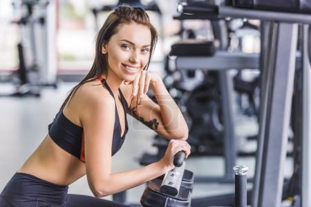 Photo pour Jeune femme attrayante se détendre à la salle de gym après l'entraînement - image libre de droit