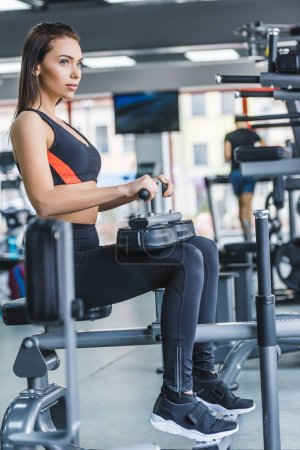 young sportive woman sitting on gym machine and looking away