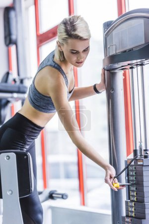 sportive young woman adding weight on gym machine
