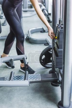 cropped shot of woman adding weight on gym machine