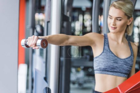 young sportive woman working out with dumbbell at gym