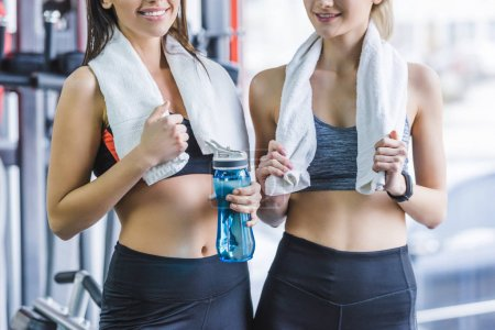 cropped shot of sportive women with towels relaxing after training at gym