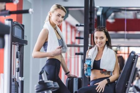 young sportive women with towels relaxing after training at gym