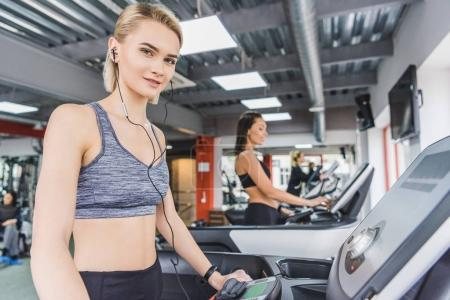 attractive sportive woman running on treadmill at gym with earphones