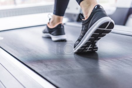 Photo for Cropped shot of woman in jogging sneakers running on treadmill - Royalty Free Image