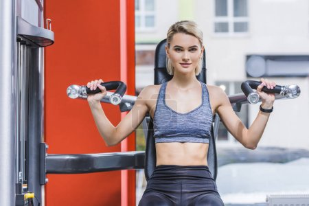 young sportive woman working out with gym machine