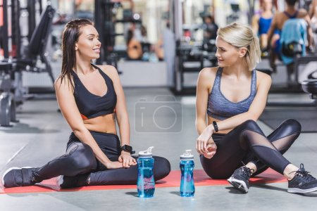 young sportive women relaxing after training at gym while sitting on yoga mat