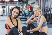 young athletic women in modern sportswear at gym looking at camera