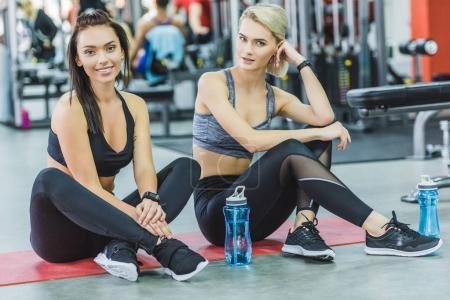 attractive sportive women sitting on yoga mat at gym