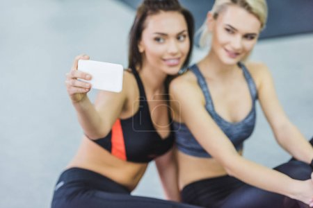close-up shot of young sportive women taking selfie at gym