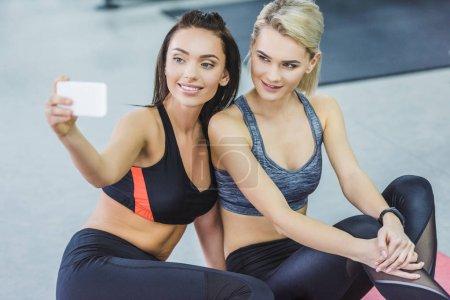 happy sportive women taking selfie at gym