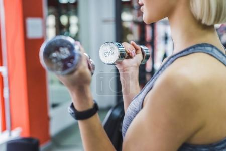 cropped shot of woman working out with dumbbells at gym