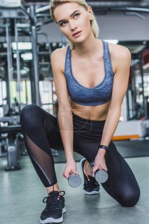young attractive woman working out with dumbbells at gym