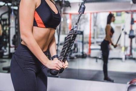 cropped shot of sportive woman doing exercise with gym machine