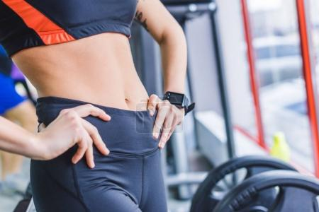 cropped shot of woman in modern sportswear with smart watch at gym
