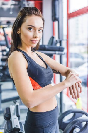 young sportive woman checking fitness tracker at gym and looking at camera