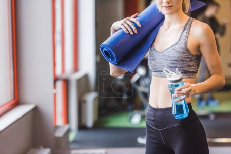 cropped shot of sportive woman with rolled yoga mat and water bottle standing at gym