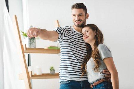 Photo pour Heureux jeune couple à la maison à la recherche quelque part - image libre de droit
