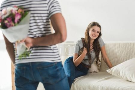 cropped shot of man hiding bouquet behind back to present it to girlfriend