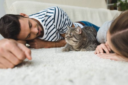 happy young couple lying on floor with tabby cat