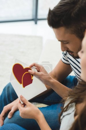 close-up shot of young couple with valentines day greeting card in envelope
