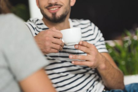 cropped shot of smiling young man drinking coffee on date with girlfriend