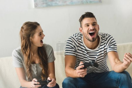 happy young couple playing games with gamepads at home