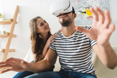 Photo for Woman looking at her excited young boyfriend in vr headset - Royalty Free Image
