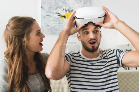 Photo for Woman looking at her shocked young boyfriend in vr headset - Royalty Free Image