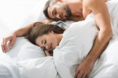 young couple sleeping together while man embracing girlfriend