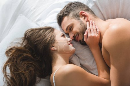 top view of smiling young couple cuddling in bed in morning