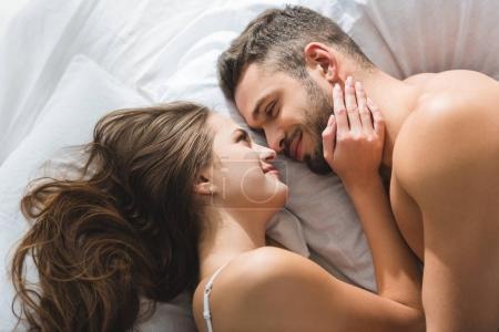 Photo pour Vue du haut du jeune couple souriant câlinant au lit le matin - image libre de droit