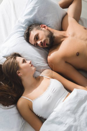 top view of young couple lying in bed and looking at each other in morning