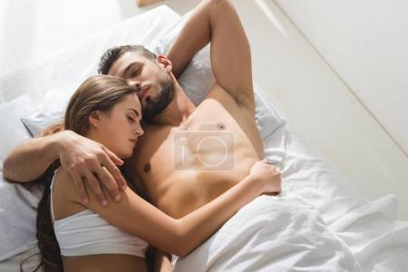 top view of young couple embracing in bed in morning