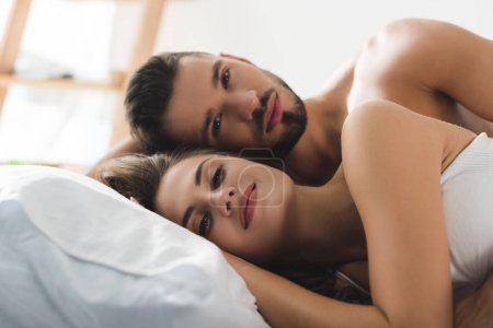 young couple relaxing in bed at morning and looking in camera