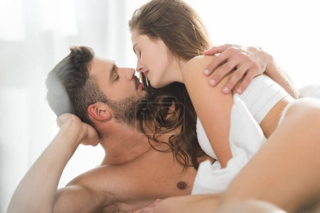 beautiful young couple kissing in bed at sunny morning