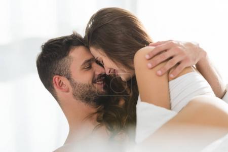 jeune couple souriant et l'embrassant dans son lit au matin