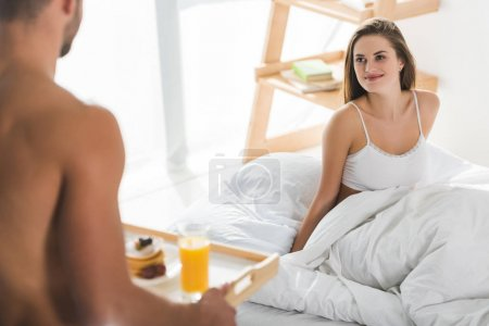 man giving breakfast in bed for smiling girlfriend at sunny morning