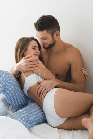 Photo for Happy young couple cuddling in bed at home - Royalty Free Image