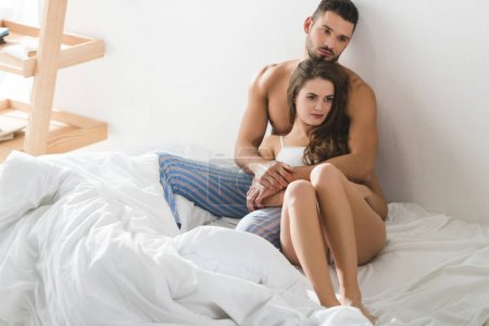 Photo for Beautiful young couple embracing in bed in morning - Royalty Free Image