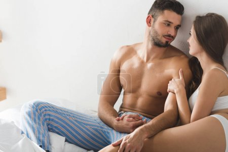 young couple sitting in bed in morning and holding hands