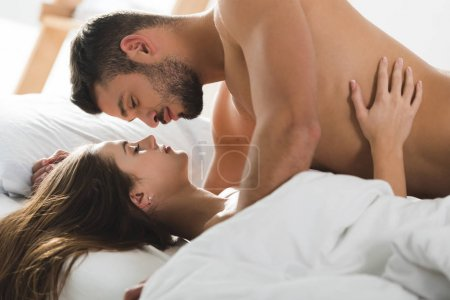 passionate young couple cuddling in bed in morning