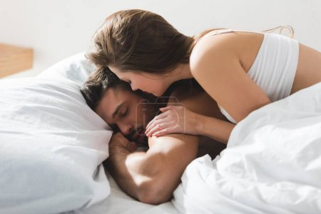 beautiful young woman lying on her sleeping boyfriend in morning