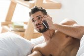 shocked overslept man talking by phone in bed in morning
